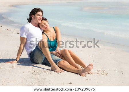 Young Couple Sitting in a Caribbean Beach - stock photo