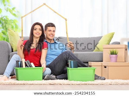 Young couple sitting in a living room and making a roof over their heads with a tape measure at home - stock photo