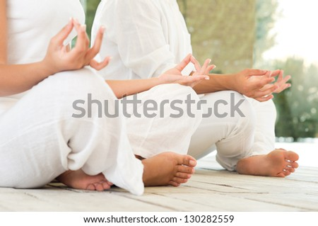 Young Couple Sitting In A Lotus Pose And Meditating - stock photo