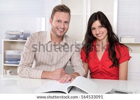 Young couple sitting in a meeting - holding hands - making investment or takes a credit.