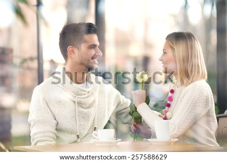 Young couple sitting in a restaurant. Happy young woman holding a white rose. - stock photo