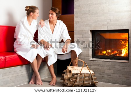 Young couple sitting in bathrobe for open fireplace, it is very romantic - stock photo