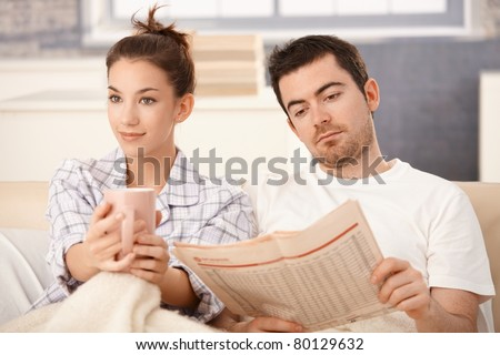 Young couple sitting in bed, man reading newspaper, woman drinking tea, smiling.? - stock photo