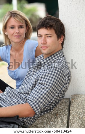 Young couple sitting in campus yard