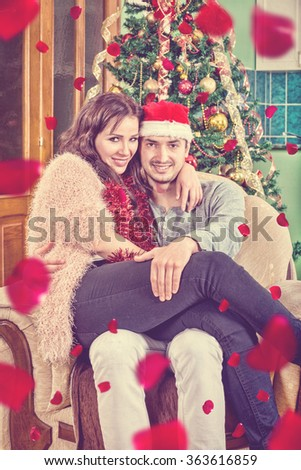 Young Couple Sitting in Chair in Their Home in New Year's and Christmas Atmosphere, Rose Petals All Around. Behind Them Is Green Tree with Ornaments. Love and Affection in the Warm Ambience. Holidays - stock photo