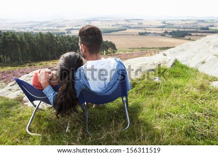 Young Couple Sitting In Chairs On Camping Trip