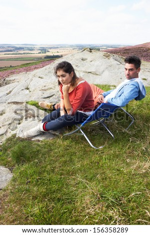 Young Couple Sitting In Chairs On Camping Trip - stock photo