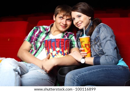 Young couple sitting in cinema and watching movie