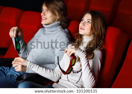 Young couple sitting in cinema and watching movie - stock photo