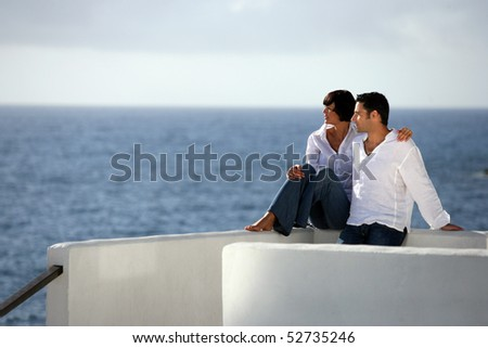 Young couple sitting in front of the sea - stock photo