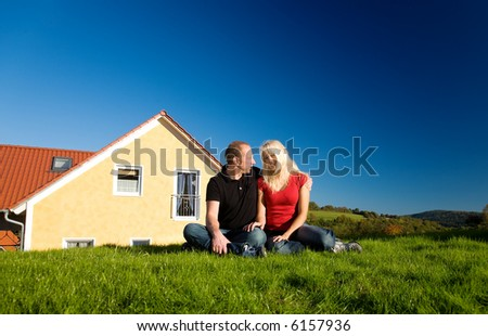 Young couple sitting in front of their country home on the lawn in the sun