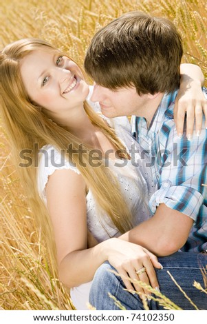 young couple sitting in grain field - stock photo