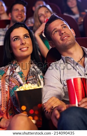 Young couple sitting in movie theater, watching film, having popcorn. - stock photo