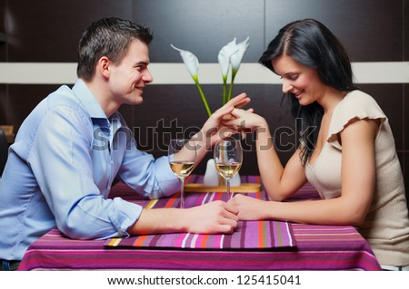 Young couple sitting in restaurant, flirting and drinking wine - stock photo