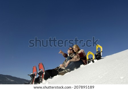 Young couple sitting in snow, woman pointing, low angle view - stock photo