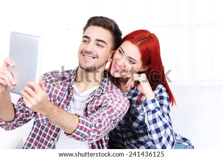 Young couple sitting in sofa with tablet in room - stock photo