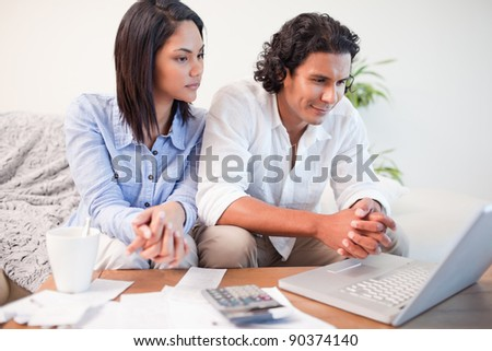 Young couple sitting in the living room doing online banking - stock photo