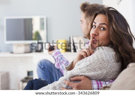 Young couple sitting in the living room watching tv. Woman is making a hush gesture. Silence sign - stock photo
