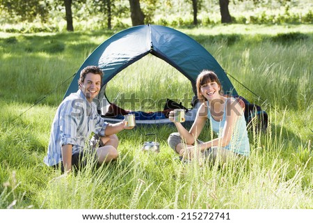 Young couple sitting near dome tent on camping trip in woodland clearing, holding mugs, smiling, portrait