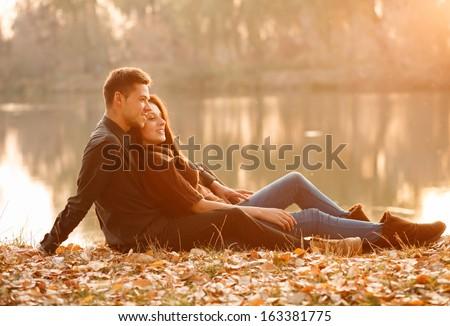 young couple sitting near lake smiling having good time sunset - stock photo