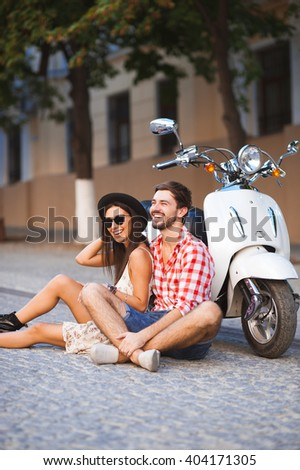Young couple sitting near white retro scooter and smiling. Happy relathionship travel concept - stock photo