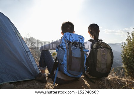 Young couple sitting next to the tent - stock photo