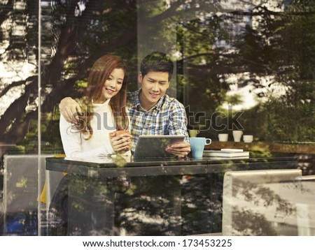 young couple sitting next to windows looking at tablet computer in cafe. - stock photo