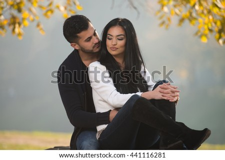 Young Couple Sitting On A Bench In The Beautiful Autumn Day