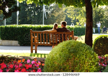Young couple sitting on a bench in the park - stock photo
