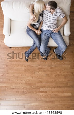 Young couple sitting on a cream colored love seat and kissing. Vertical shot