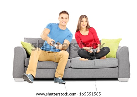Young couple sitting on a modern couch and playing video games isolated on white background - stock photo