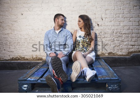 young couple sitting on a pallet against brick wall - stock photo