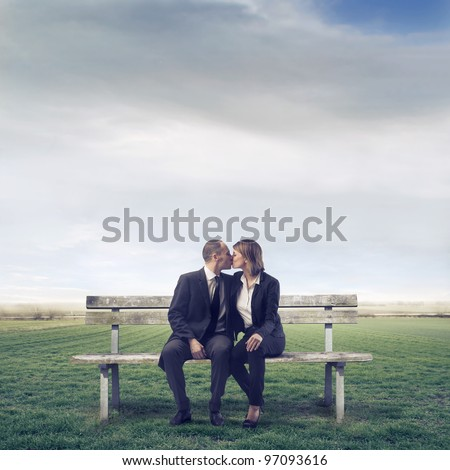 Young couple sitting on a park bench and kissing