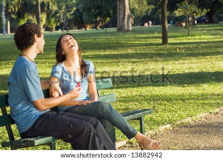 Young couple sitting on a park bench. They are laughing as he holds a red flower. Young couple sitting on a park bench. They are smiling as he shows her a red flower.  Horizontally framed photograph