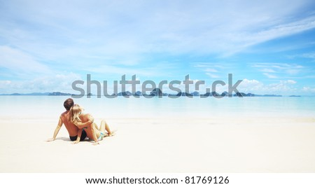 Young couple sitting on a resort's white sand and looking to a far islands on the horizon - stock photo