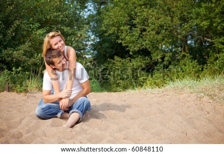 young couple sitting on a sand - stock photo