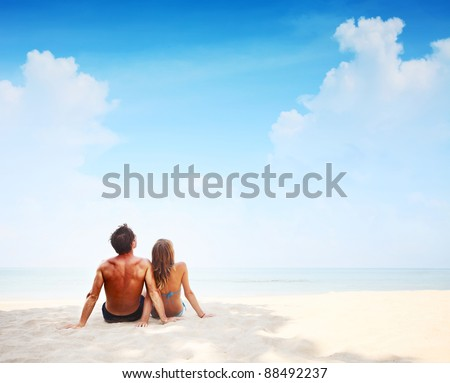 Young couple sitting on a sand and looking to a blue tropical sky