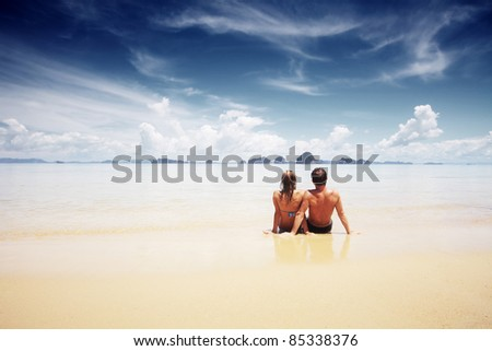 Young couple sitting on a sand and looking to a sea - stock photo