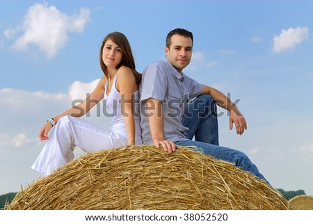 young couple sitting on a straw bale - stock photo