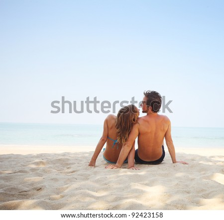 Young couple sitting on a tropical sandy beach