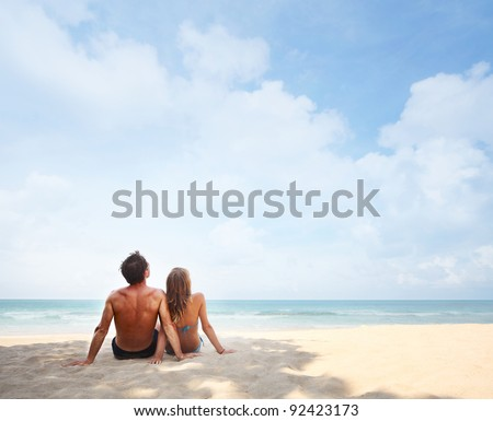Young couple sitting on a tropical sandy beach - stock photo