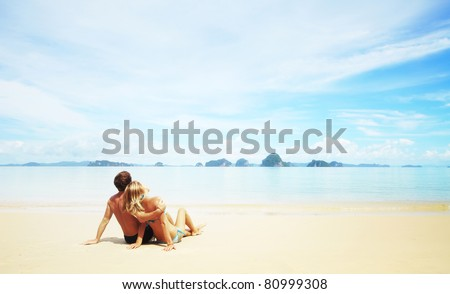 Young couple sitting on a white sand and looking to a blue sky with clouds