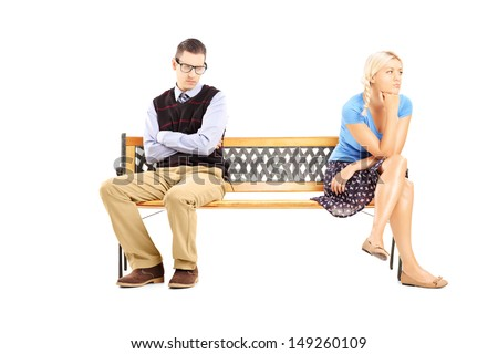 Young couple sitting on a wooden bench after having an argument isolated against white background - stock photo