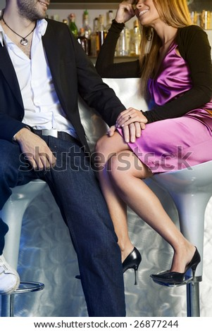 young couple sitting on bar stools and holding hands - stock photo