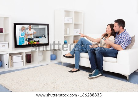 Young Couple Sitting On Couch Watching Cookery Show - stock photo