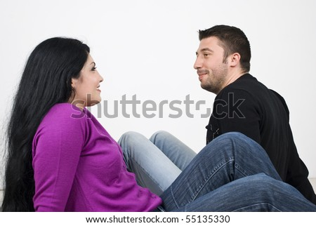 Young couple sitting on floor face to face in profile looking each other and having a conversation