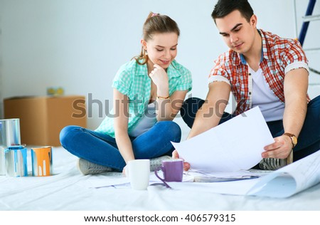 Young couple sitting on floor with apartment plan - stock photo