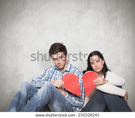Young couple sitting on floor with broken heart against weathered surface - stock photo
