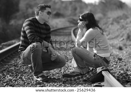 Young couple sitting on railway tracks (Black and White photo) - stock photo