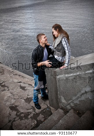 Young couple sitting on riverbank